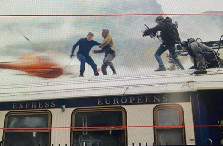 Tom Cruise acena do topo de trem em movimento enquanto filma Missão Impossível