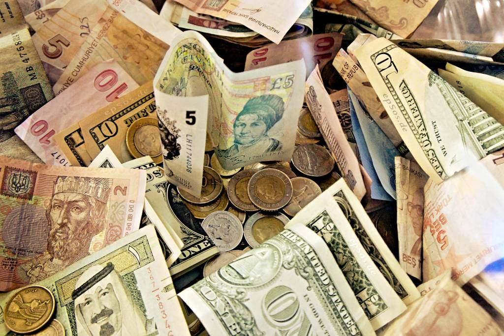 É melhor pagar em dólar ou no dinheiro local em destinos turísticos internacionais?